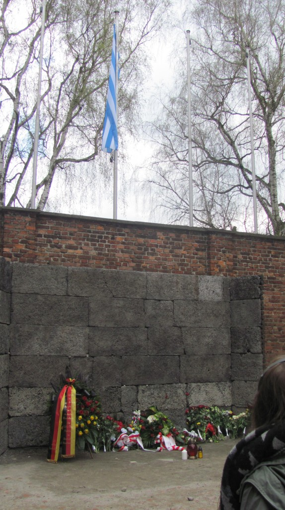 This firing wall is in a courtyard with all of the windows covered whether boarded up or bricked. This way no one else in the camps could see what went on inside. The flag above the wall today represents the stripes of the uniforms the prisoners wore.